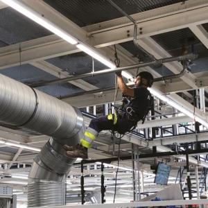Ein Mann hängt von mit Seilen von der Decke in einer Industriehalle und installiert Deckenluechten