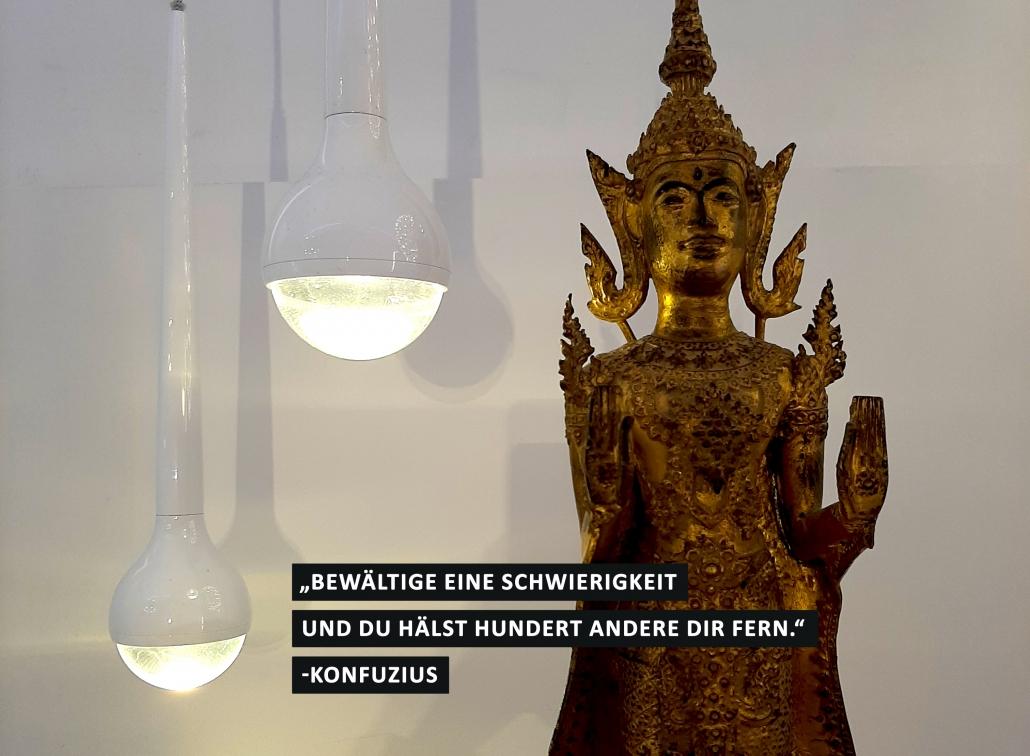 """Zwei tropfenförmige Leuchten, neben einer goldenen Statue von einem indischen Budda. Dazu der Spruch """"Bewältige eine Schwierigkeit und due hälst hunderte andere dir fern."""" von Konfuzius"""